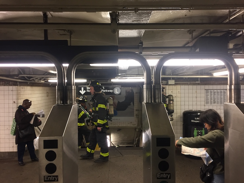 Firemen standing in front of the L train station, blocking entrance to commuters. Caused by an electrical fire in an underground MTA vault.