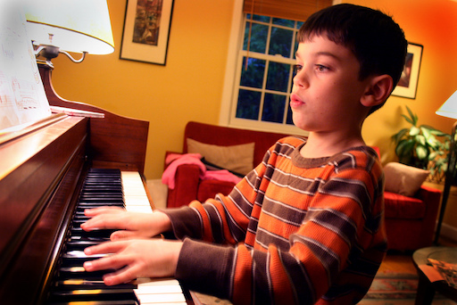 A boy practicing his piano skills
