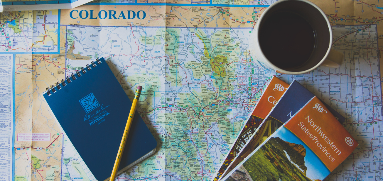 A Colorado state map with a pencil and notepad placed over it - represents the concept of doing local search engine optimization.