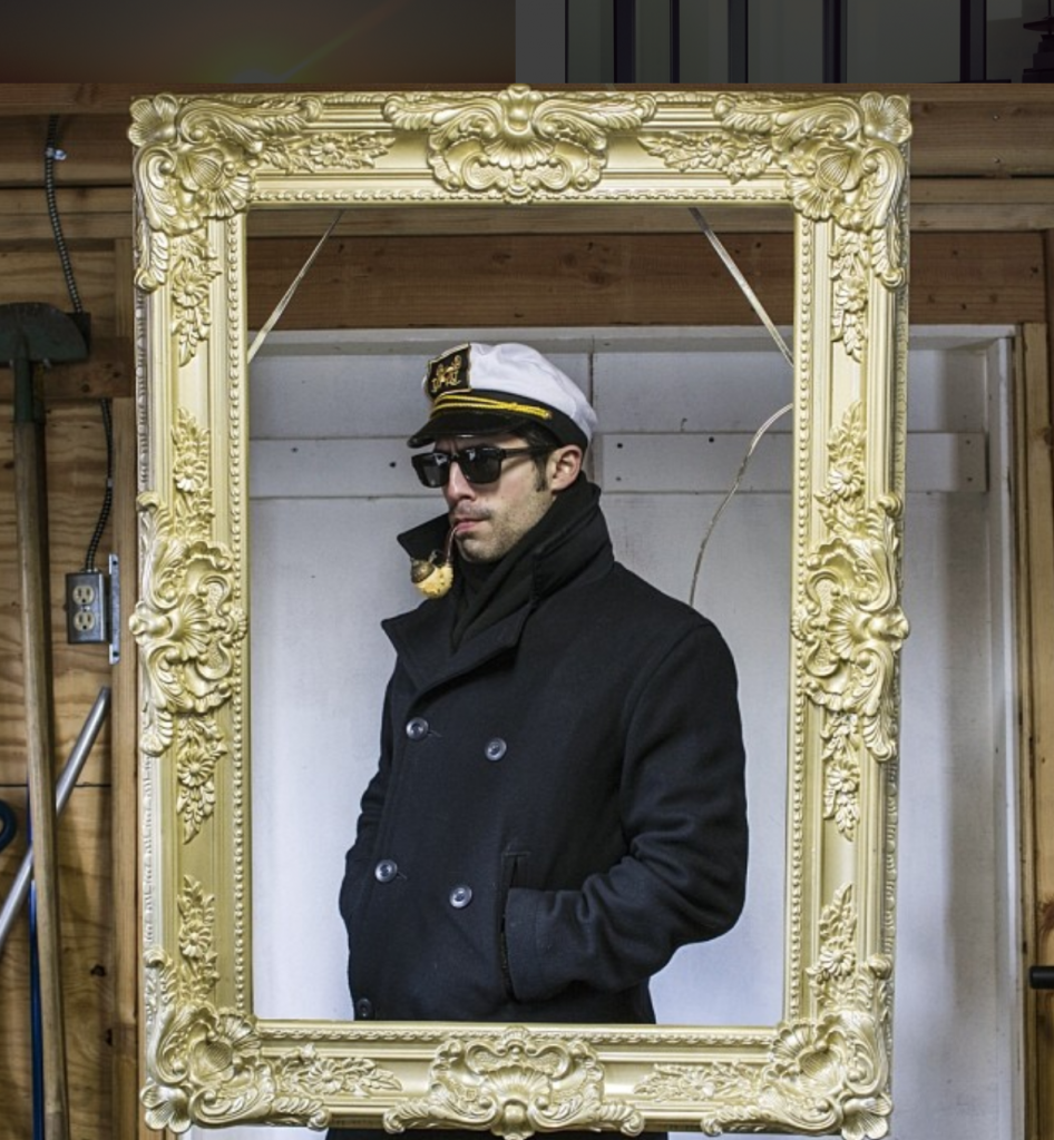 Michael Sorace, posing in a captain's outfit, framed with an ornate golden frame in a garage.