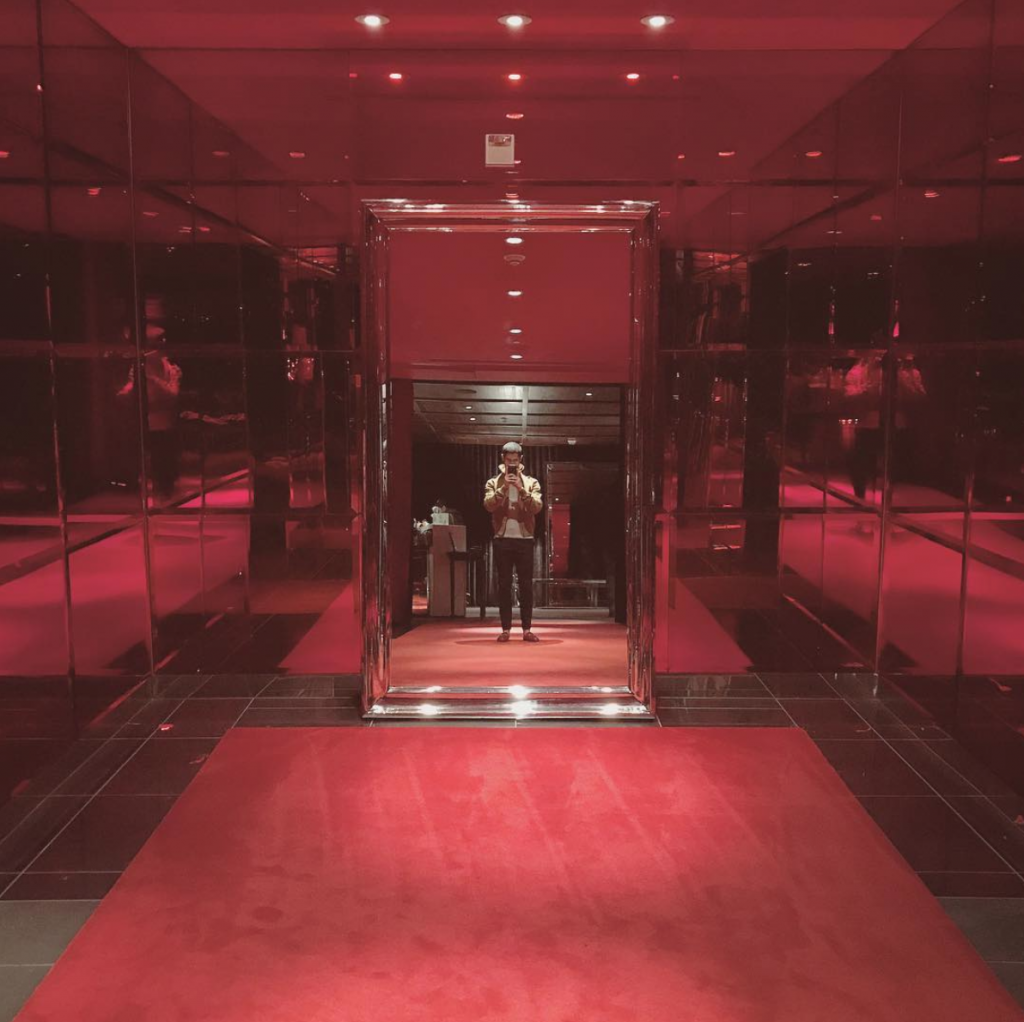 Michael Sorace, dressed in Saint Laurent, taking a selfie in a luxurious red mirrored room in a 5 star hotel.