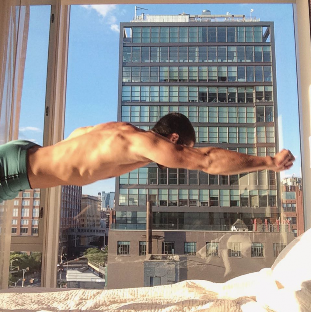 Michael Sorace, shirtless, jumping onto a bed in the NYC Meatpacking Standard Hotel.