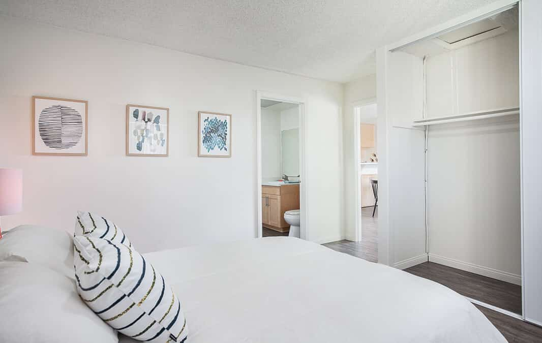 bedroom with white walls, white bed covers, and white closet,