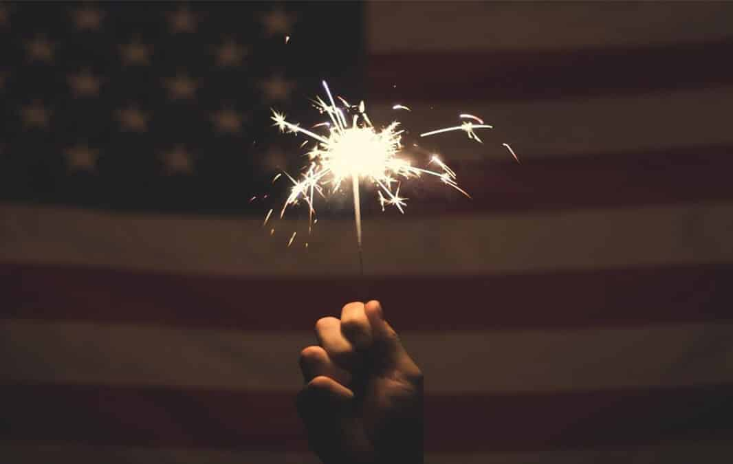 a hand holding a sparkler with the American flag behind