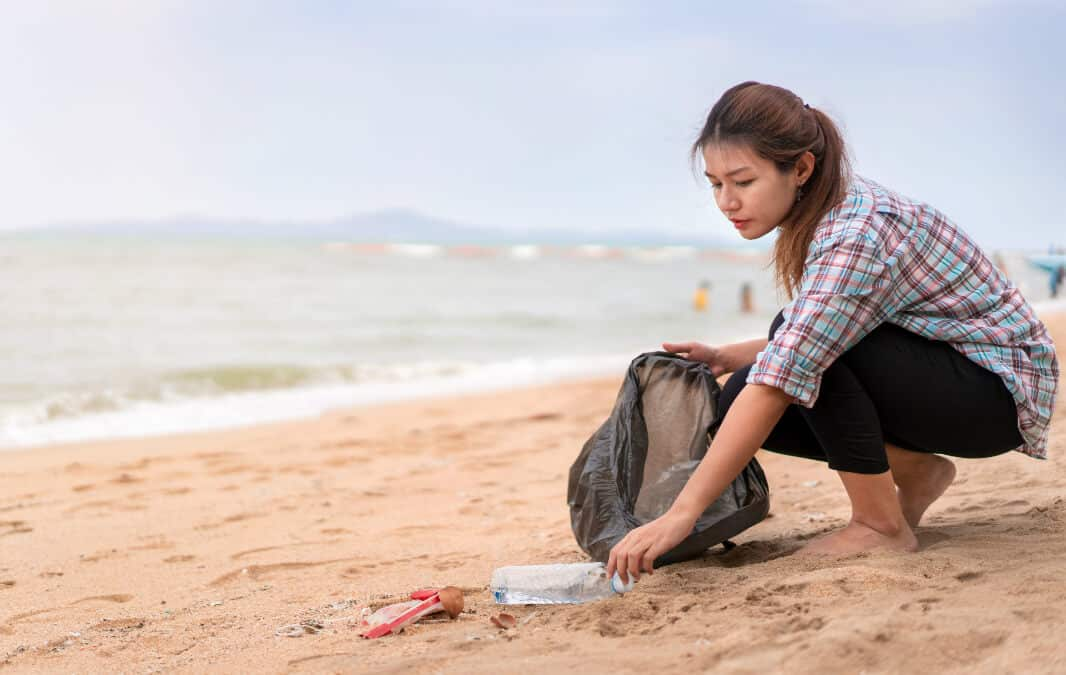 a woman picking up trash left on the beach