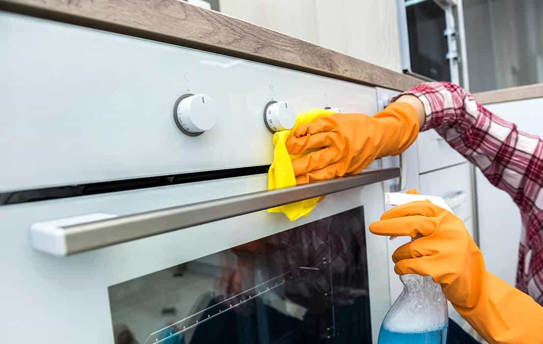 person wearing orange gloves cleaning a white oven