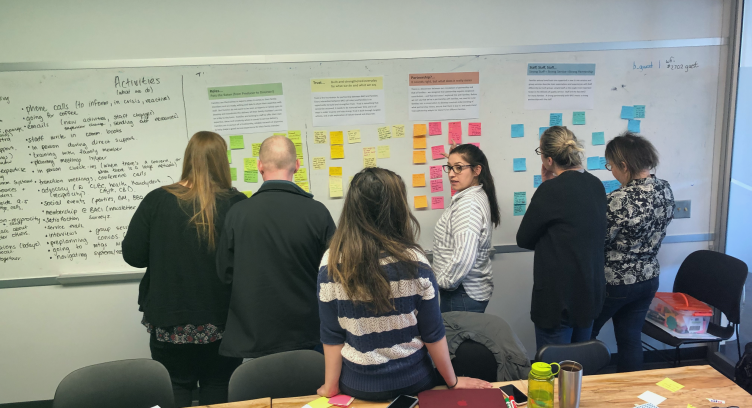 a group of people look at sticky notes on a white board
