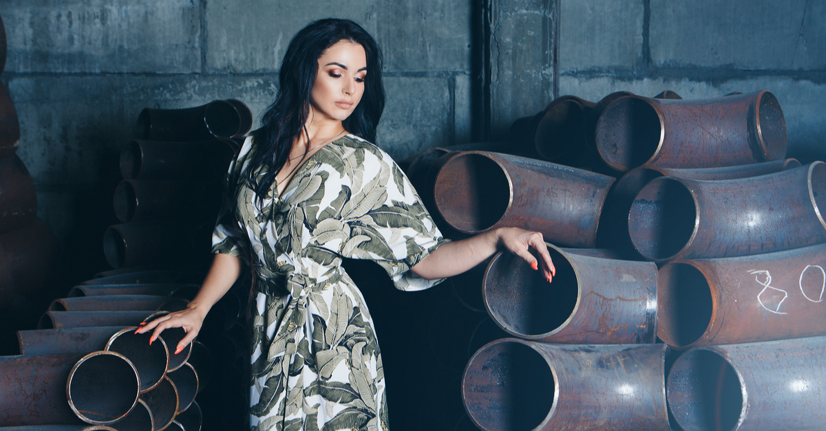 model business concept, factory floor, building materials, beautiful brunette with bright red manicure, in dress and shoes posing among metal pipes.