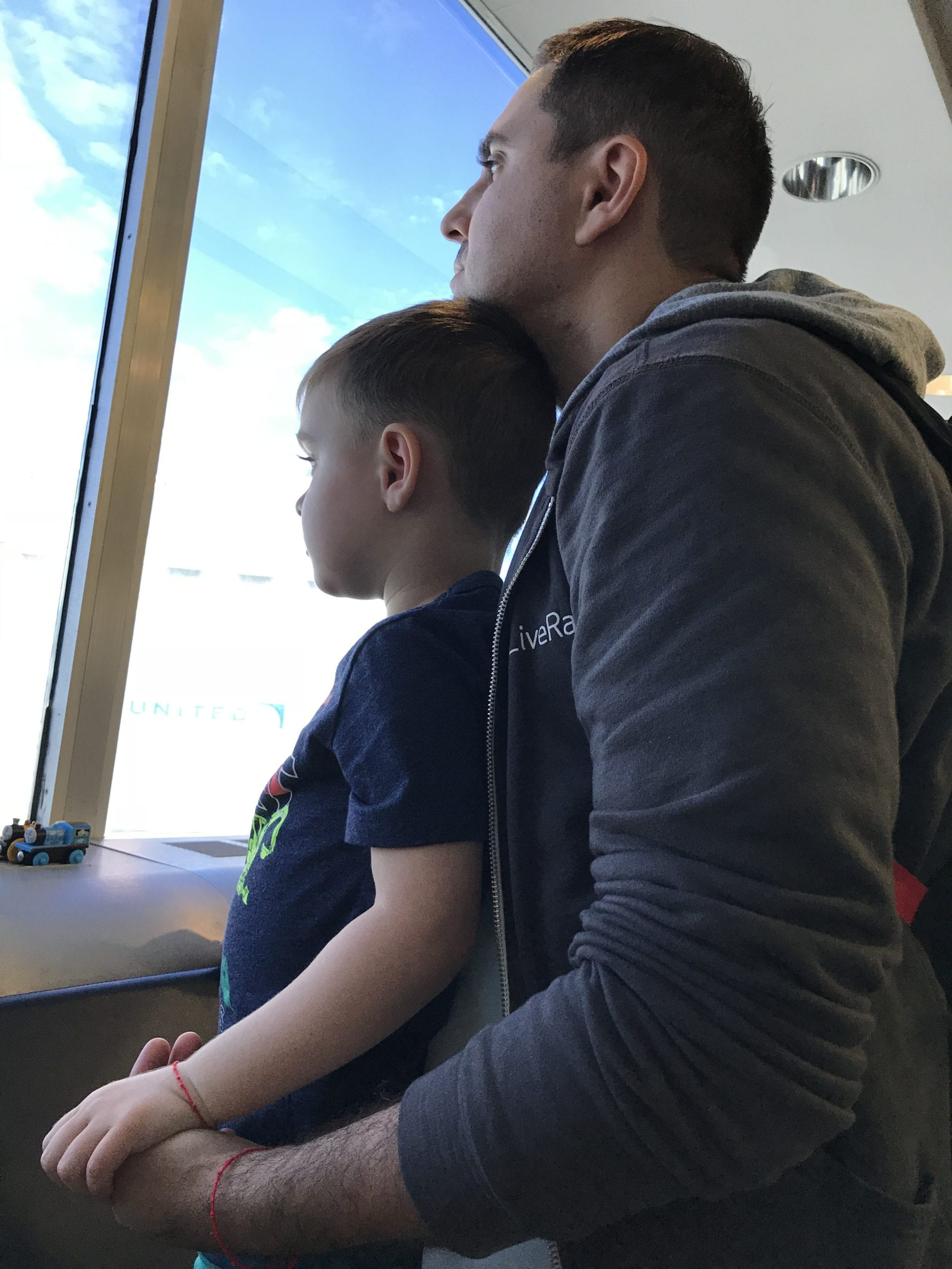 Image of Anna's husband and son, looking out the airport window. Anna is owner of Olegana Travel Boutique.