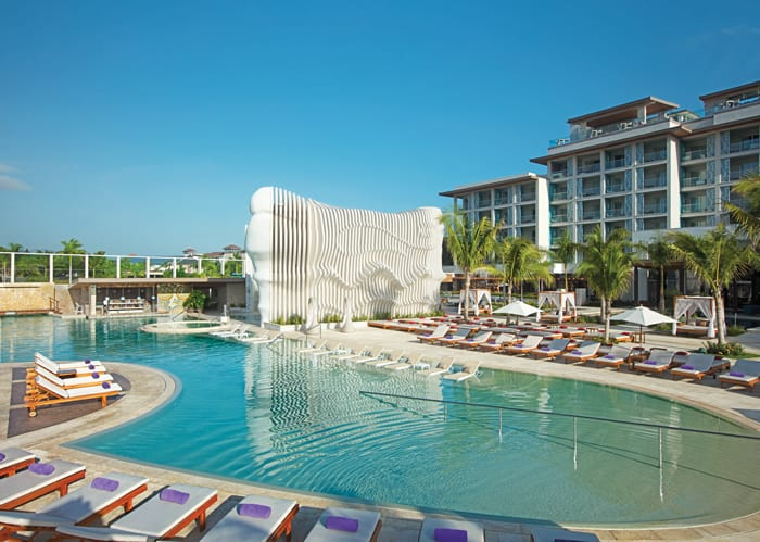 Outside with the resort pictured and a main pool with Freestyle swim-up bar