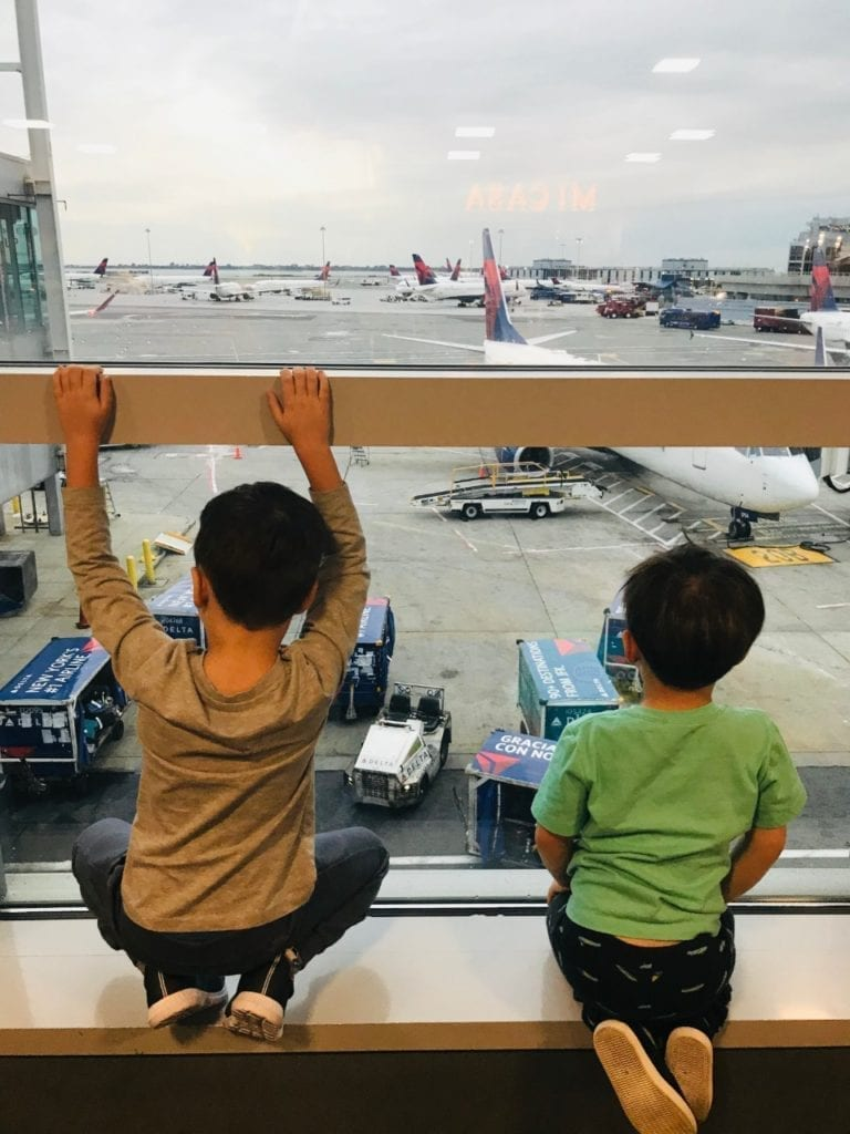 Two boys looking at the airplanes in the airport