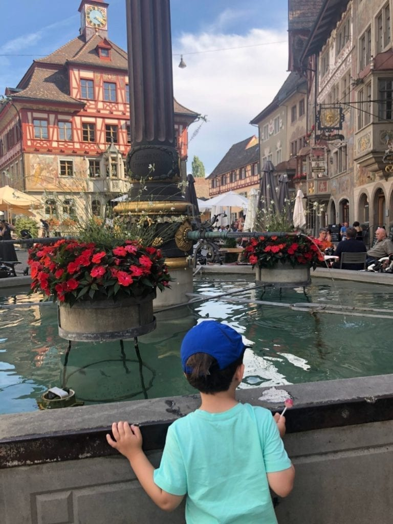 A boy looking at the fountain with flowers in a medieval town of Stein am Rhine in Switzerland