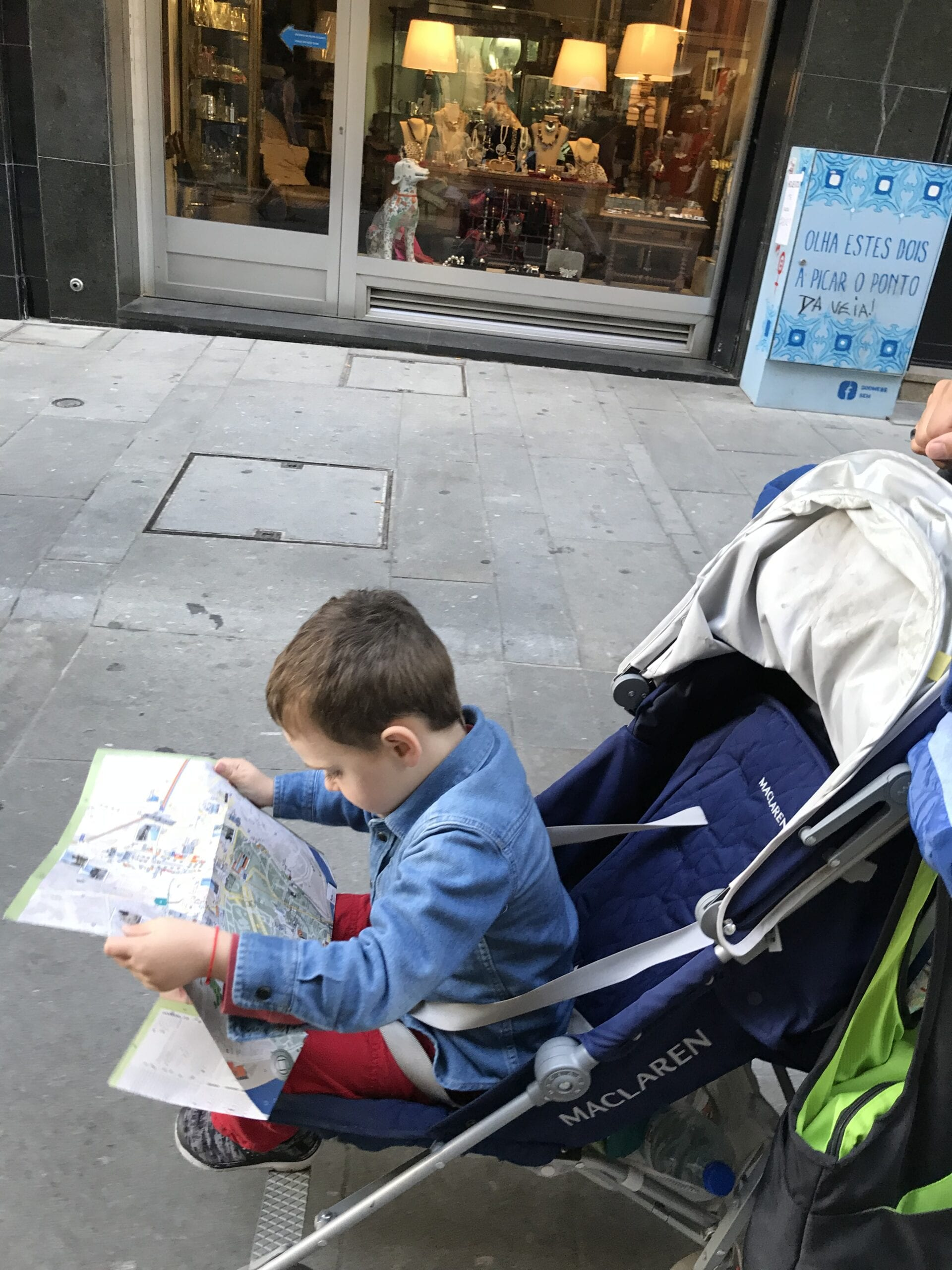 Child in a stroller reading a map