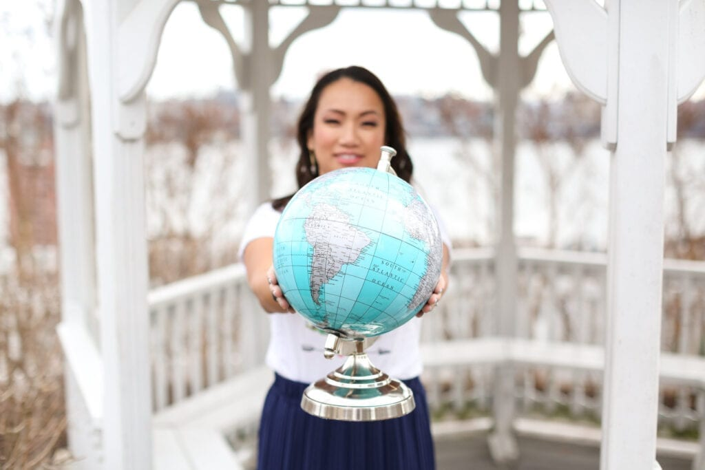 Asian woman, holding a globe. Photo of Clara Wang Photography by MikiFoto + Co. Where to Go in 2021 – Must-Visit Destinations of the Year