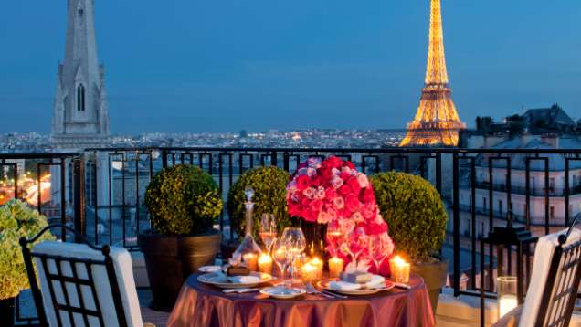 Romantic dinner in a restaurant in Paris, view of Eiffel tower, candles, flowers, Paris vacation, anniversary dinner.