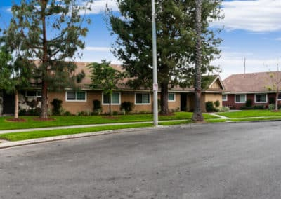 Exterior View of The Evergreens Apartment Homes surrounded by Green plants and trees