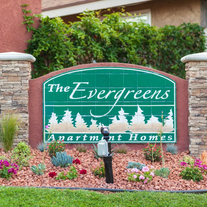 The Evergreens Apartment Homes Sign surrounded by plants