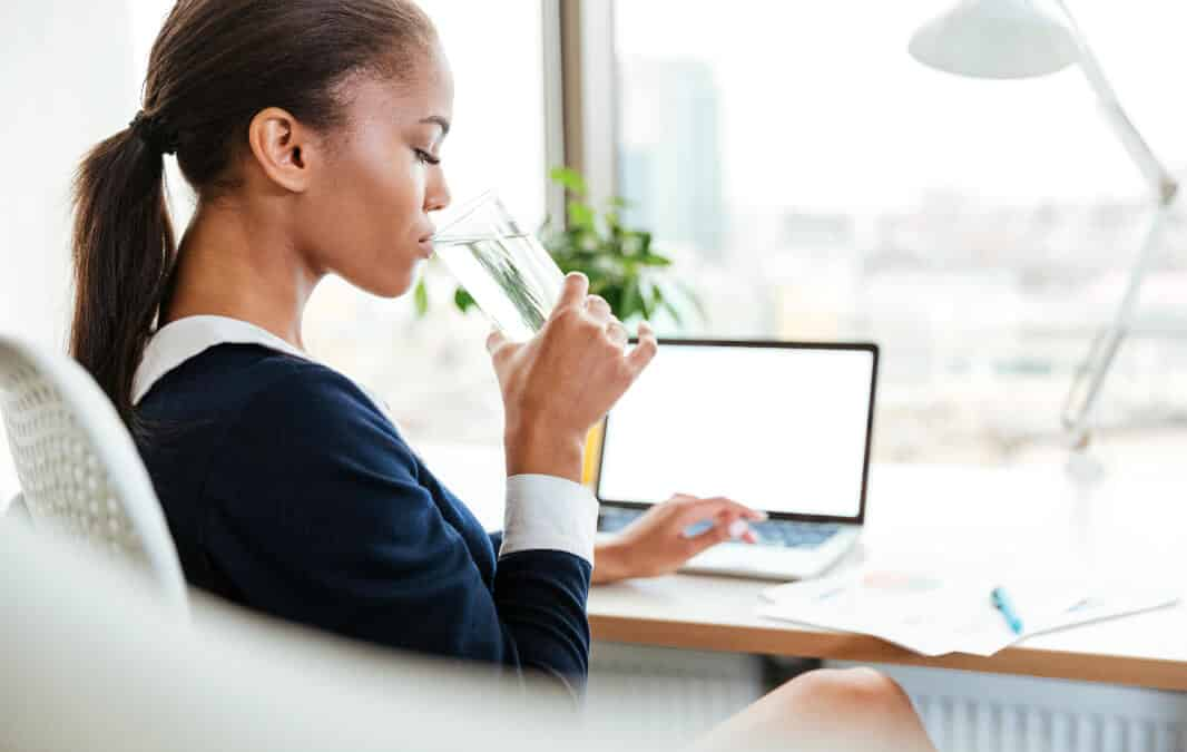 Woman drinking a glass of water while sitting in front of laptop