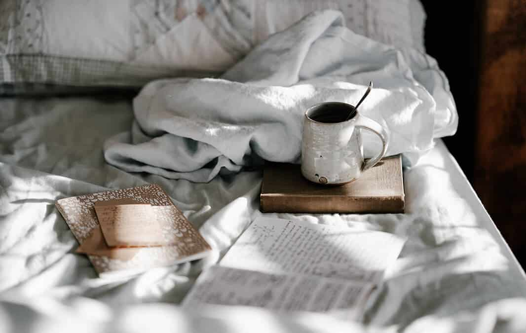 Books on a bed with tea