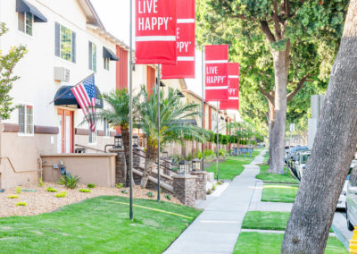 Walkways with Live Happy Flag near grassy yard and trees