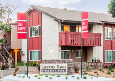Lakewood Manor Sign with two red Live Happy flags
