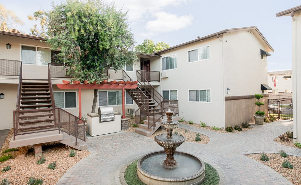 Exterior apartment view showing fountain, pathways, and outdoor stairs