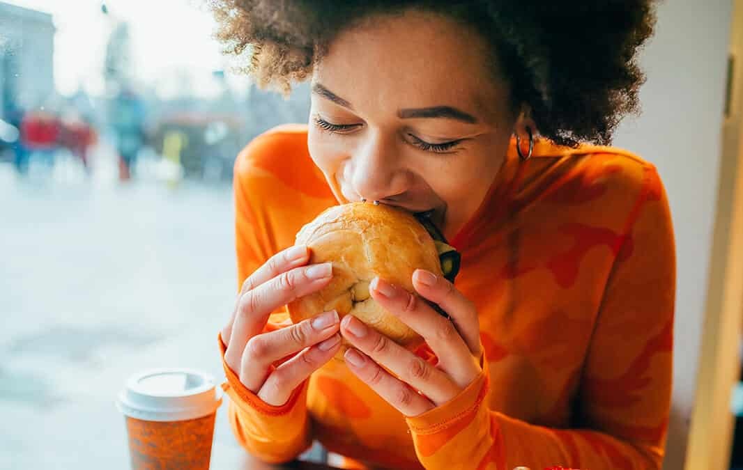 woman in orange shirt eating a bagel