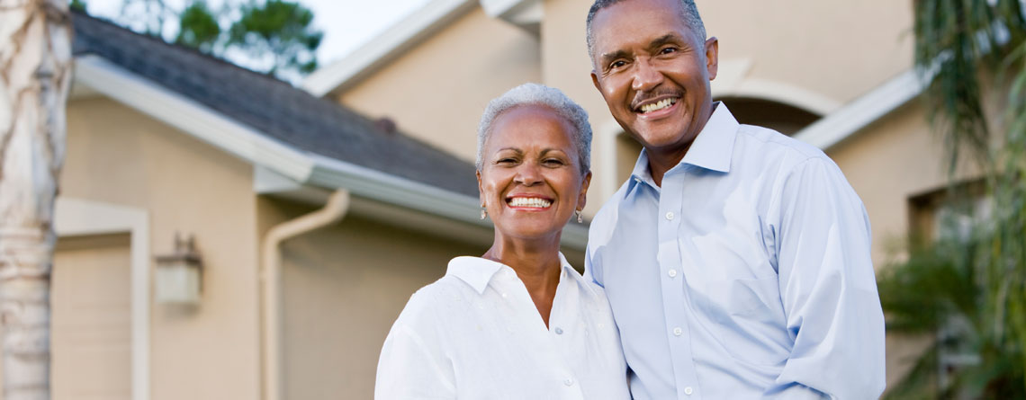 homeowner couple smiling in front of home