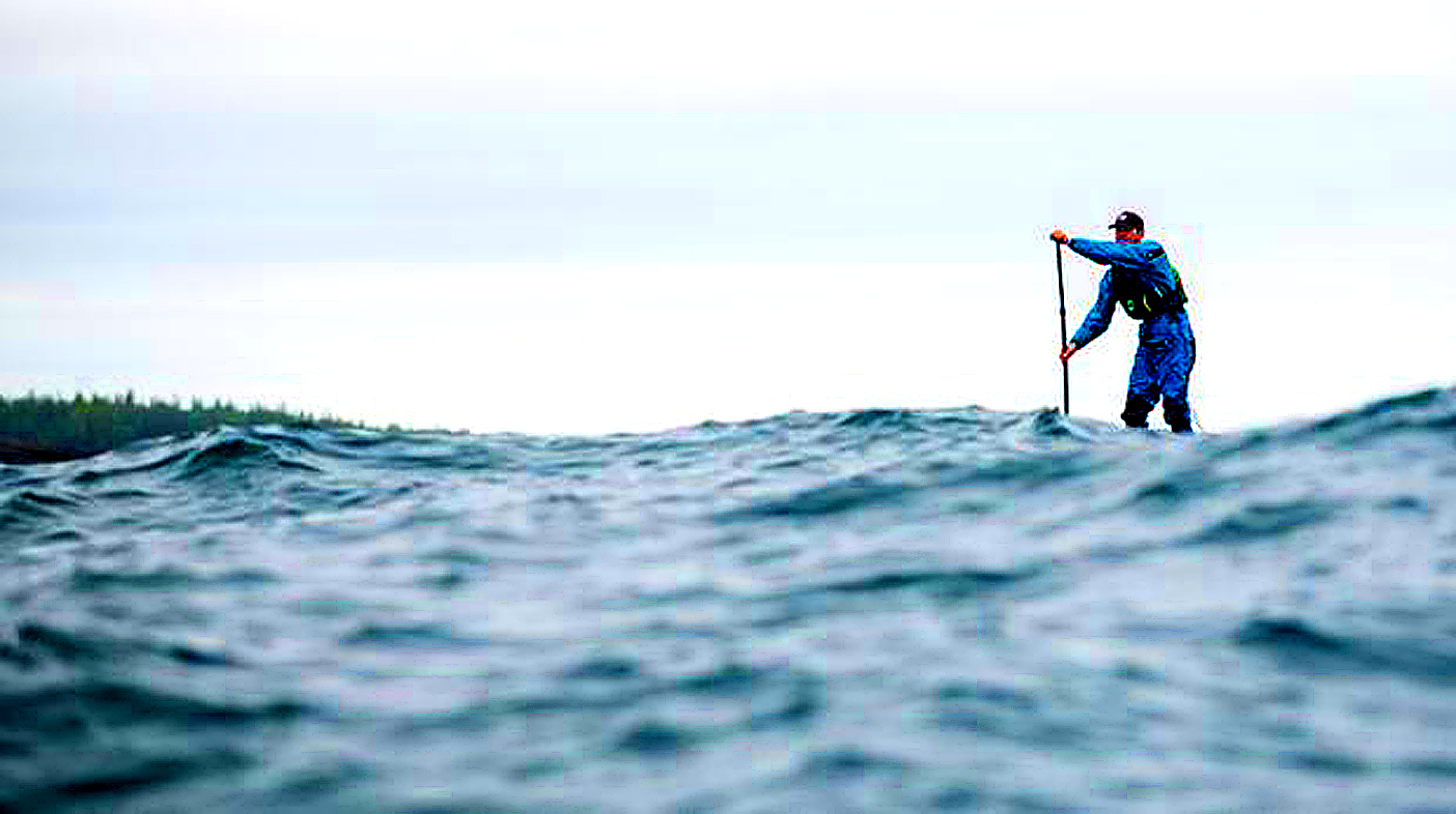 How to spend one wondrous week. Jack paddles around Scoville Point in rough water, heading back towards Rock Harbor. | Image Credit: Aaron Black-Schmidt, 2020.