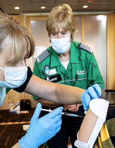 Every adult will be offered Covid vaccine by autumn, said Matt hancock. Deirdre Barr of St John Ambulance watches as volunteers practise injecting fake arm pieces in London. Image Credit: Richarf POHLEohle, 2021.