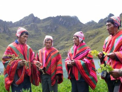 Local men conversing near a lake in the andes mountain wearing native cusquenan clothing. Experience authentic indigenous cultures on a custom Peru tour with Southern Crossings.
