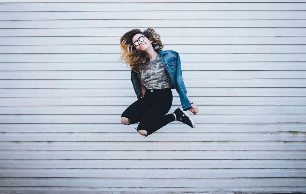 A jumping woman wearing jean jacket