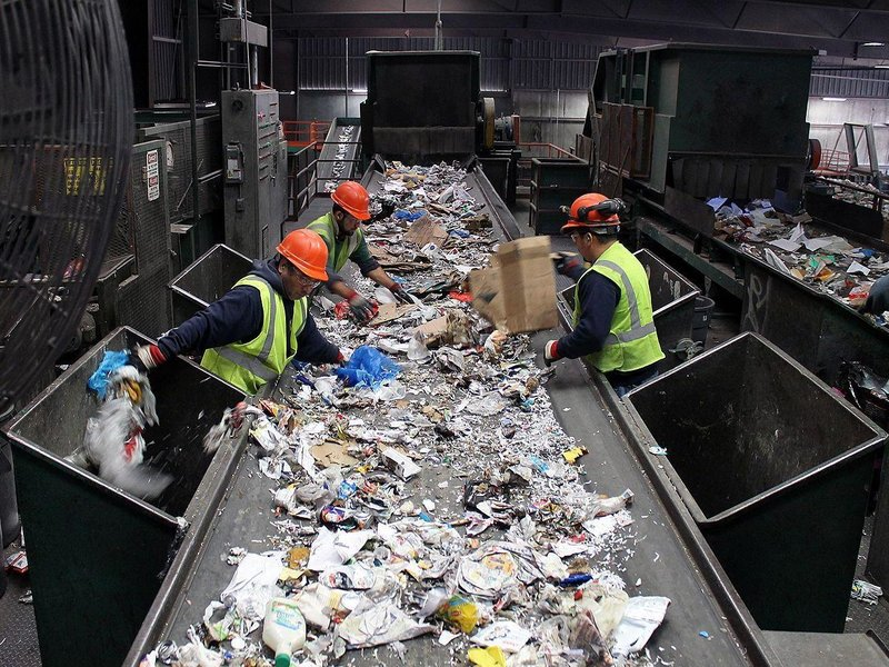 Workers sorting out recyclables from trash on a conveyor belt