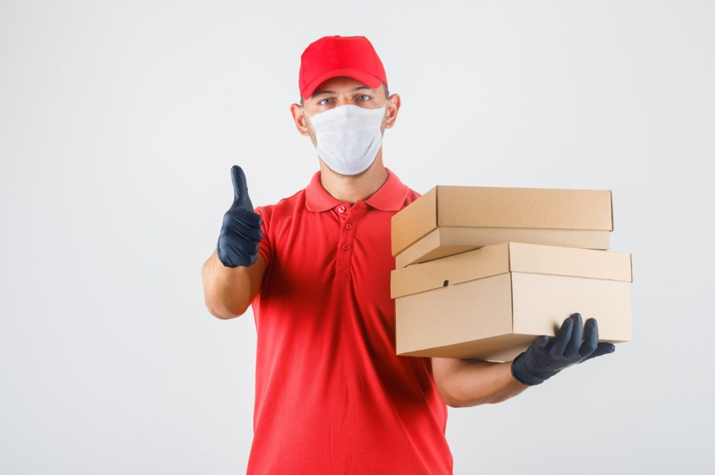 Employee holding boxes wearing a mask