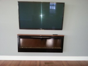 "50"" Panasonic LED panel wall mounted above an in wall electric fireplace"