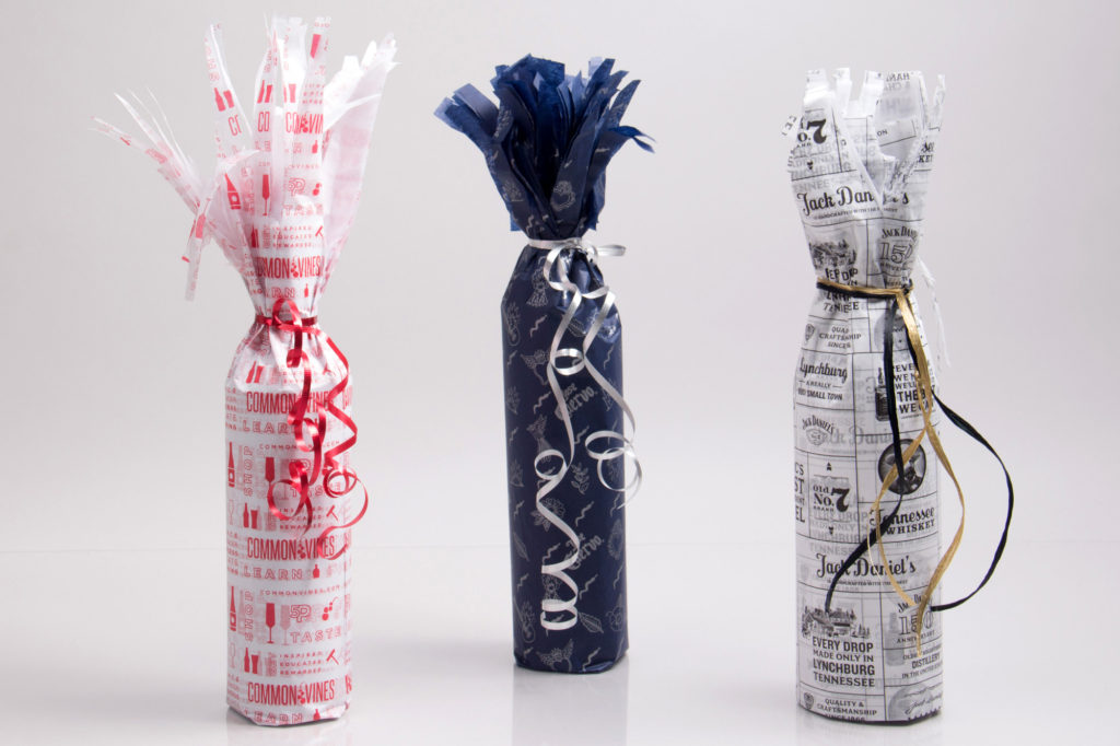 Wrapping bottles in tissue paper with ribbon ties