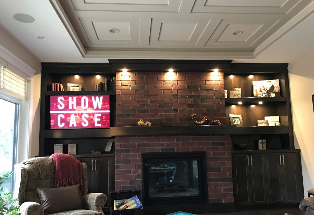 mounted television next to a brick fireplace and window