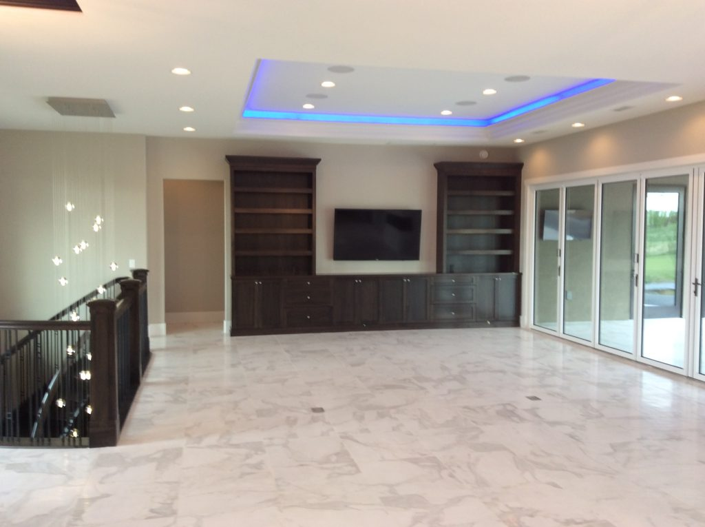 mounted tv in a room with new flooring and automated coloured lights