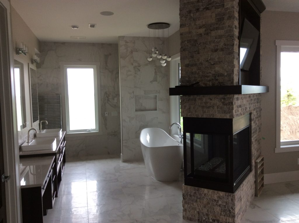 Mounted tv in a bathroom above a fireplace