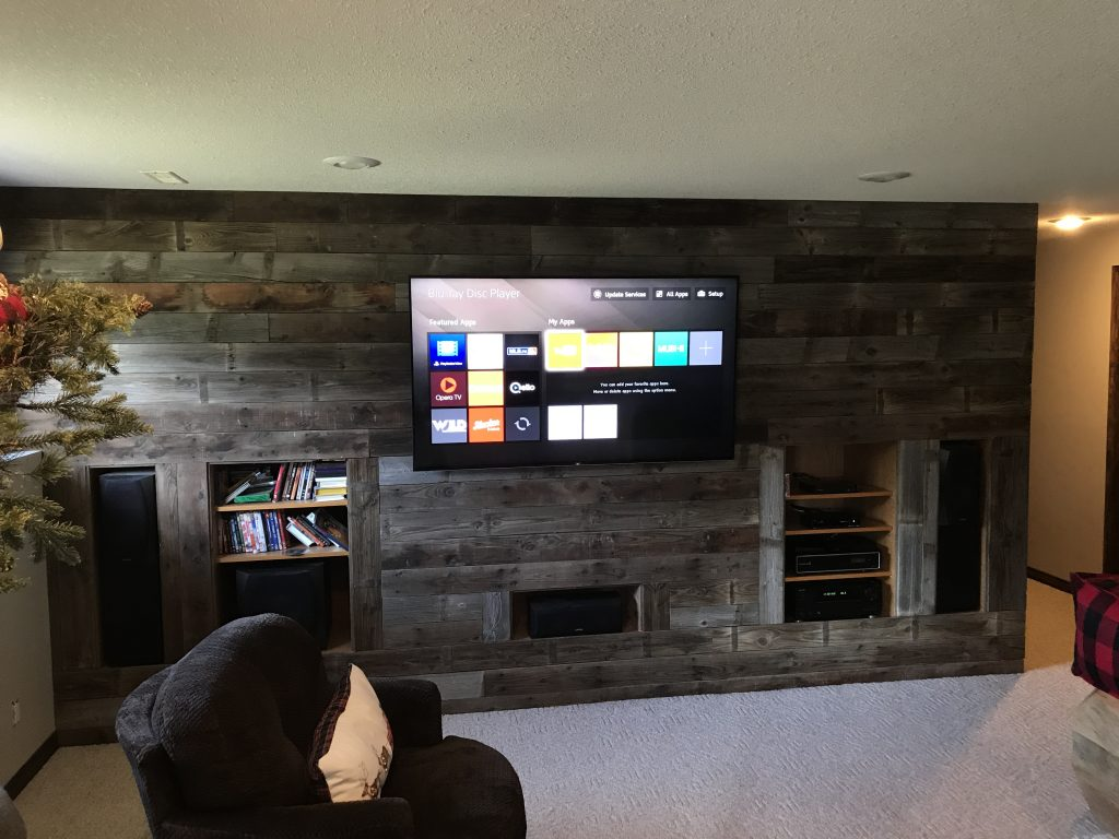 Living room theatre setup with wood wall panels and a mounted television