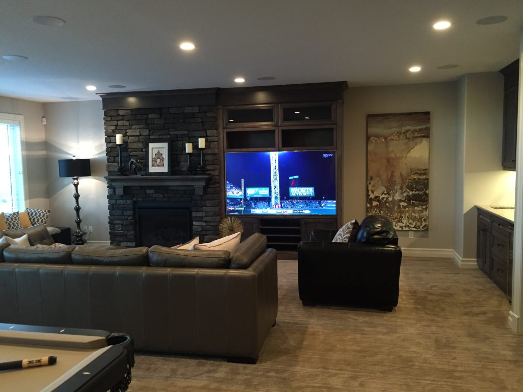 Large tv in a basement with a bar and a pool table