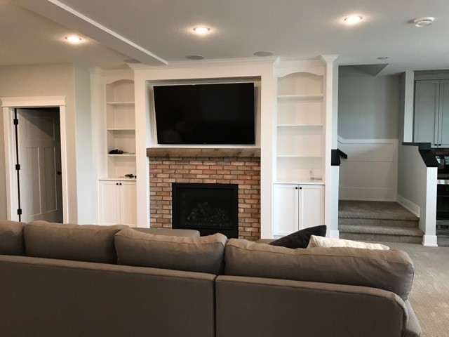 Mounted tv above a fireplace in the basement