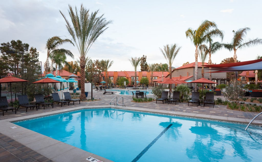 Pool at Corona Pointe Resort with outdoor seating and umbrellas