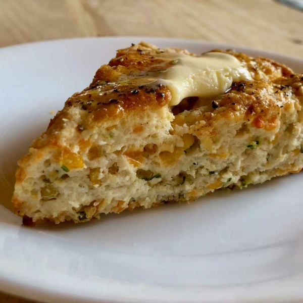 Roasted corn chive scone with butter on a plate