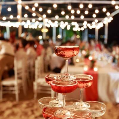 Pyramid from glasses of red wine on wedding party. Close-up of the pink champagne or wine pyramid in ceremony party.