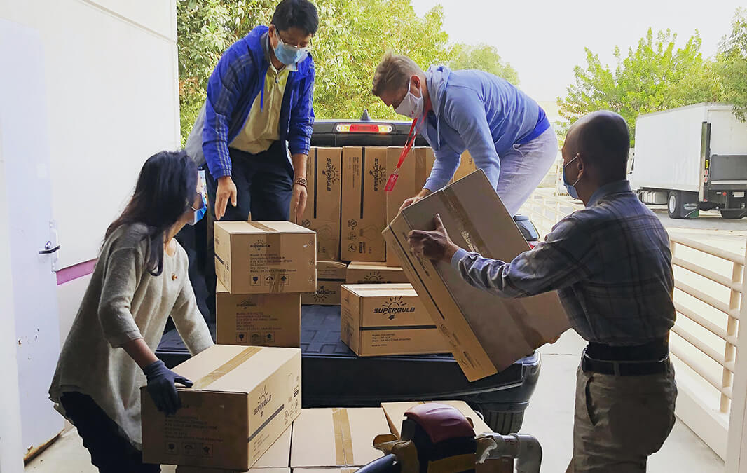 four people loading a truck with moving boxes