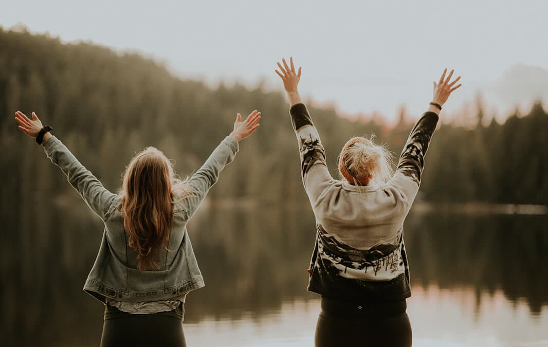 Two women with arms raised facing a lake