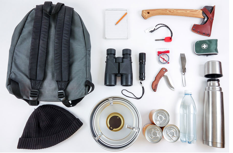 An overhead view of essential Bug-Out Bag supplies neatly organized on the floor.