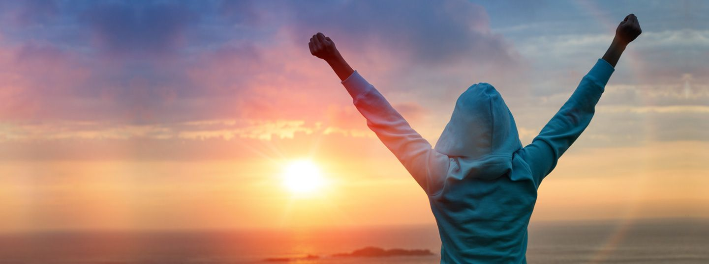 woman raising her hands goals sunrise testimonial