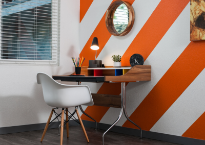 Office desk against orange and white striped wall